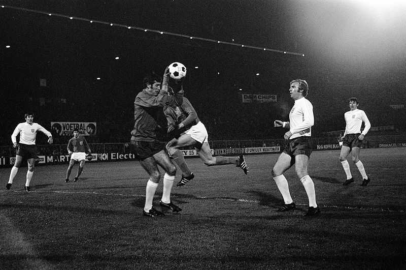 Peter Bonetti saves a football with opponents and teammates look on in a football match aganist the Netherlands on 5 November 1969 (© Eric Koch, CC0)