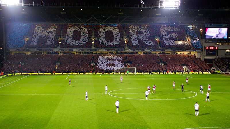 West Ham fans display Moore and 6 as a tribute to Bobby Moore twenty years after his death, in the stand which bears his name, at The Boleyn Ground, London (© Philosophy Football, CC BY 2.0)