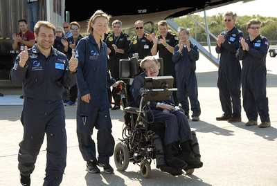 Well-wishers greet noted physicist Stephen Hawking (in the wheelchair) at the Kennedy Space Center Shuttle Landing Facility after a zero gravity flight. Next to him at left are Peter Diamandis, founder of the Zero Gravity Corp.