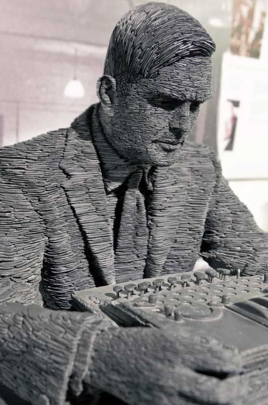 Statue of Turing by Stephen Kettle at Bletchley Park, commissioned by Sidney Frank, built from half a million pieces of Welsh slate. (© Antoine Taveneaux, CC BY-SA 3.0)