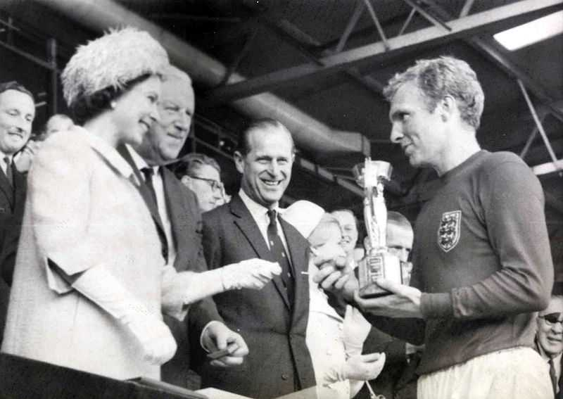 This photograph shows the Queen presenting the 1966 World Cup to Bobby Moore, captain of the victorious England team. The match was played between England and West Germany on 30 July 1966 at Wembley Stadium.
