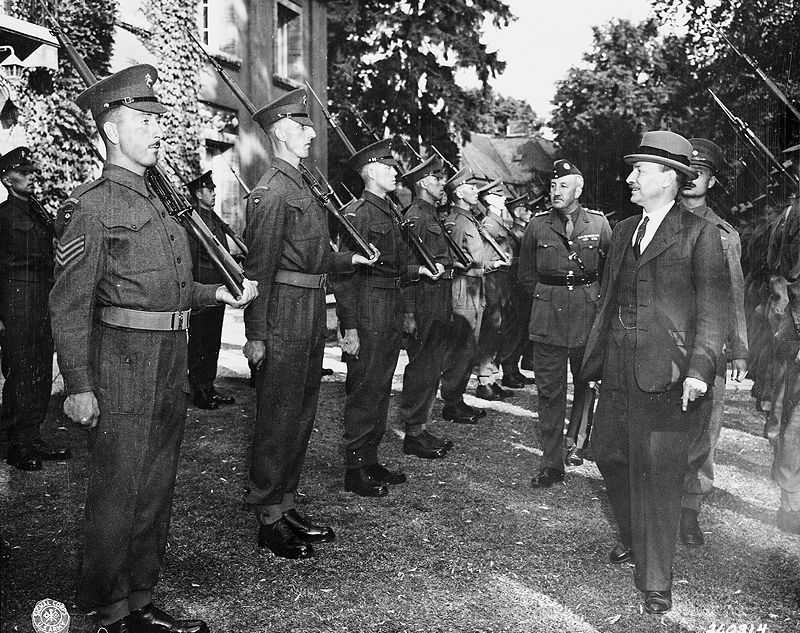 British Prime Minister Clement Attlee inspects the honor guard, consisting of Scots Guards, on the lawn of his residence during the Potsdam Conference